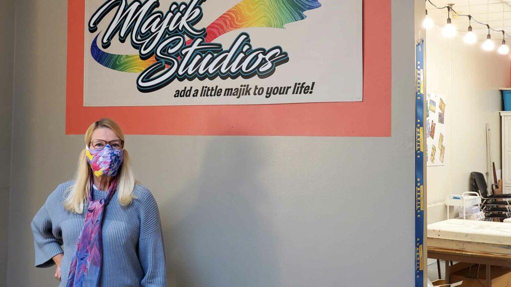 Pam Granger stands in front of her studio sign, Majik Studios, Asheville, NC.