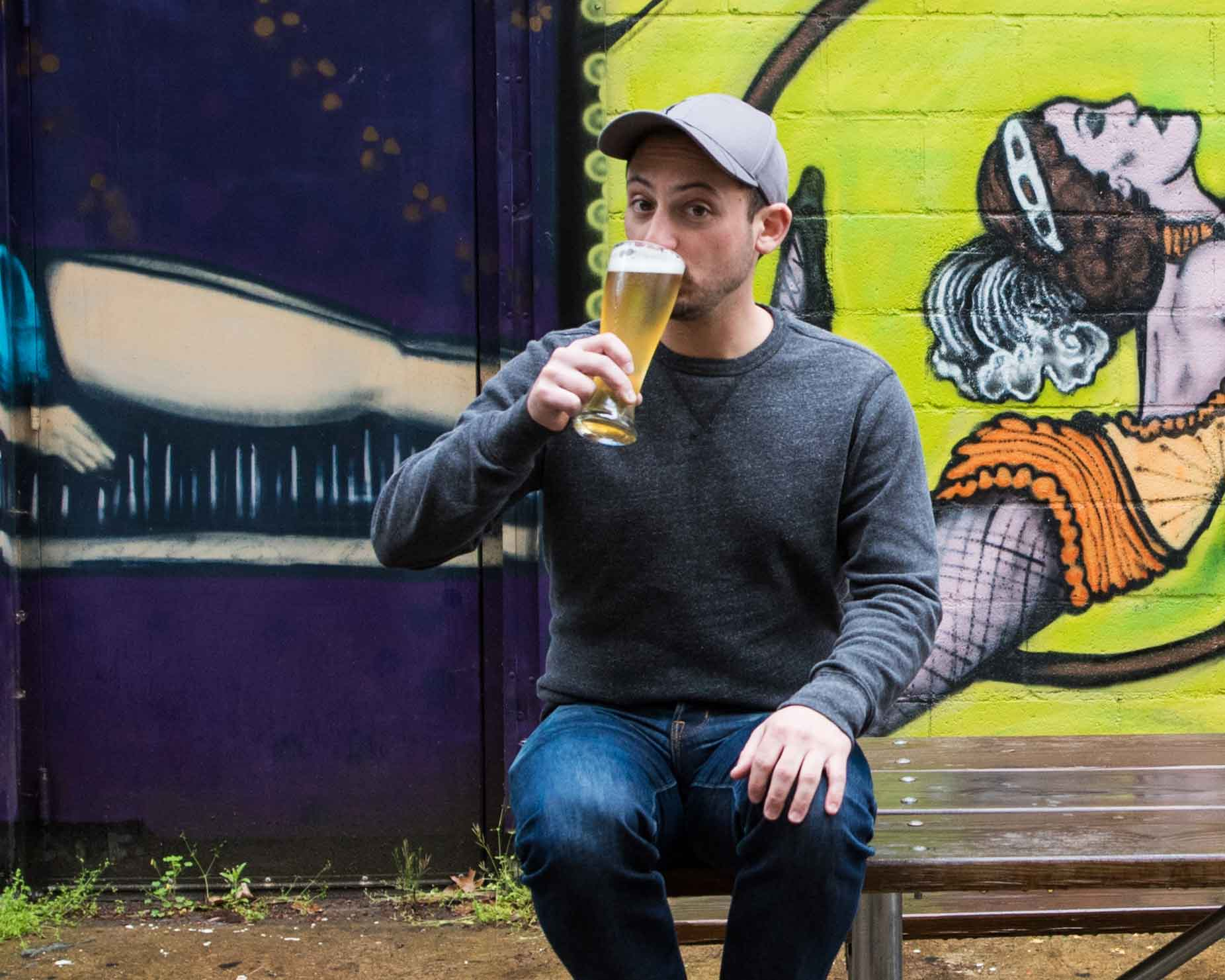 Founder of HiWire Brewing on a picnic table sipping a beer in front of a mural—Mountain BizWorks.